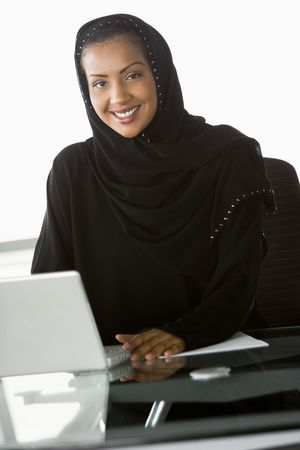 Businesswoman in office with laptop smiling (high key/selective focus) Stock Photo - 3171238