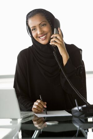 Businesswoman in office by laptop on telephone smiling (high key/selective focus) Stock Photo - 3171119