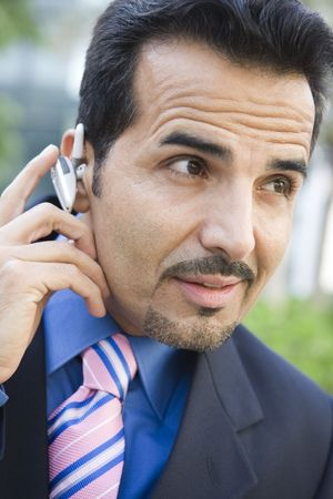 handsfree telephones: Businessman outdoors wearing headset (selective focus)