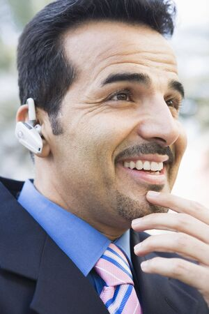 handsfree telephones: Businessman outdoors wearing headset and smiling (selective focus) Stock Photo