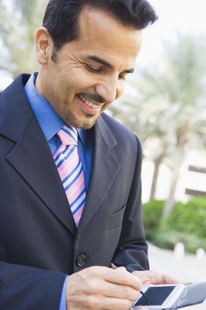 personal digital assistant: Businessman outdoors using personal digital assistant and smiling (high keyselective focus)