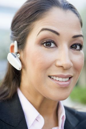 Woman wearing headset outdoors smiling (selective focus) photo