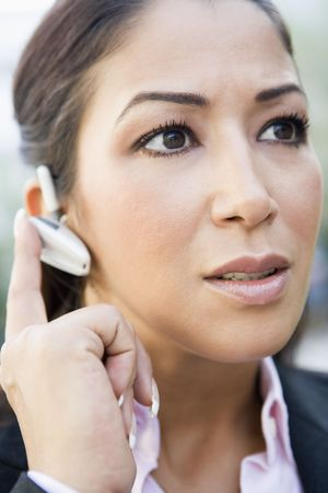 handsfree telephones: Woman wearing headset outdoors (selective focus) Stock Photo