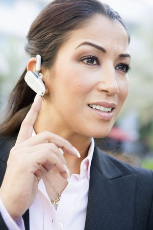 handsfree telephones: Woman wearing headset outdoors smiling (selective focus) Stock Photo