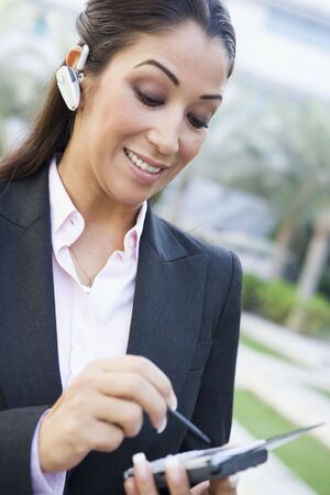 handsfree telephones: Woman wearing headset outdoors and using personal digital assistant smiling (selective focus)