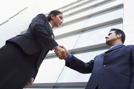 Two businesspeople outdoors by building shaking hands (high key/selective focus) Stock Photo - 3171302