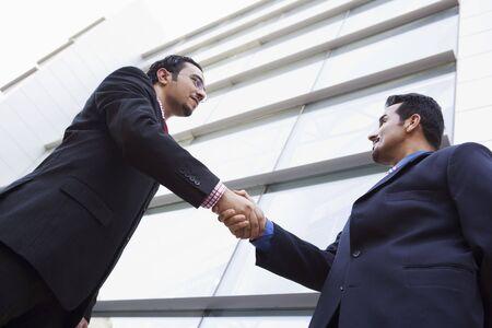 manos estrechadas: Dos hombres de negocios al aire libre mediante la construcción de estrechar la mano (clave de alta  selectiva enfoque)