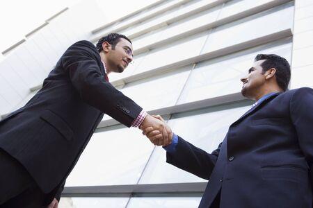 manos estrechadas: Dos hombres de negocios al aire libre mediante la construcci�n de estrechar la mano (clave de alta  selectiva enfoque)