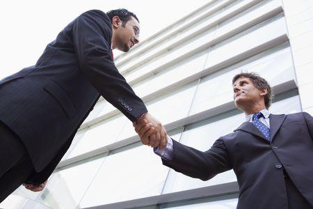poign�es de main: Deux hommes d'affaires en construisant en plein air une poign�e de main (haute cl�  s�lective focus)  Banque d'images