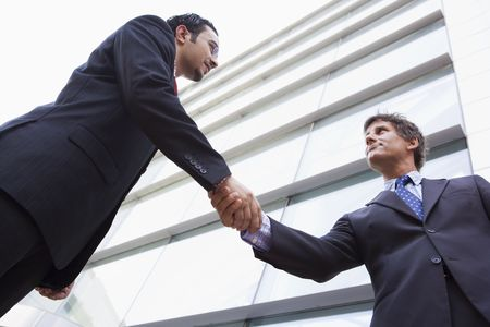caucasoid race: Two businessmen outdoors by building shaking hands (high keyselective focus)