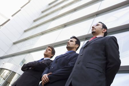 Three businessmen standing outdoors by building (high keyselective focus) photo