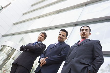 east meets west: Three businessmen standing outdoors by building (high keyselective focus) Stock Photo