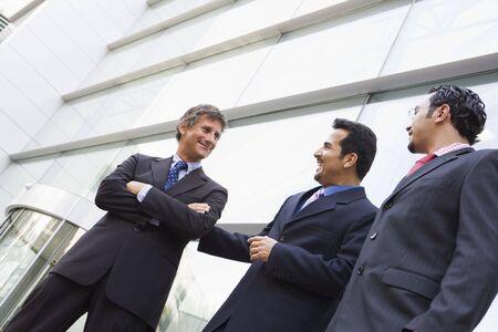 manos estrechadas: Tres hombres de negocios de pie al aire libre mediante la construcción de hablar y sonreír (clave de alta  selectiva enfoque)  Foto de archivo