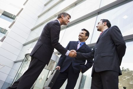 iş adamı: Three businessmen standing outdoors by building shaking hands and smiling (high keyselective focus)