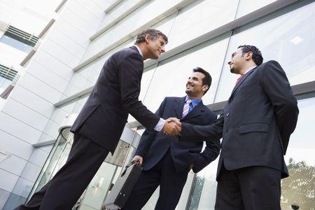 dandose la mano: Tres hombres de negocios de pie al aire libre mediante la construcci�n de darle la mano y sonriendo (clave de alta  selectiva enfoque)