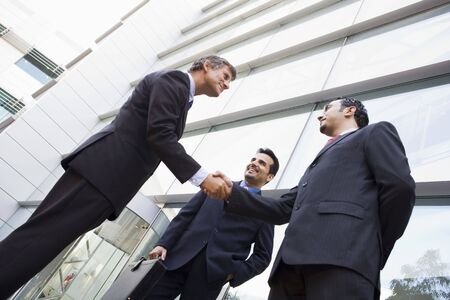 international people: Three businessmen standing outdoors by building shaking hands and smiling (high keyselective focus)