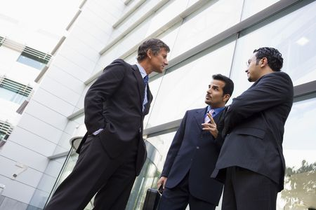 Three businessmen standing outdoors by building talking (high key/selective focus) Stock Photo - 3171133