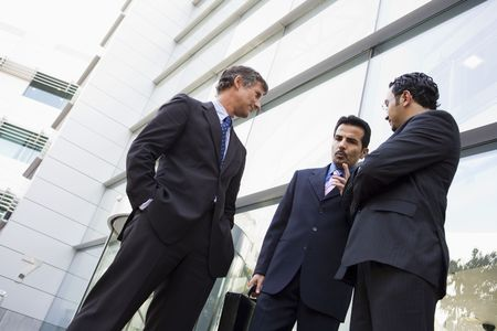 east meets west: Three businessmen standing outdoors by building talking (high keyselective focus)
