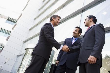 manos estrechadas: Tres hombres de negocios de pie al aire libre mediante la construcci�n de darle la mano y sonriendo (clave de alta  selectiva enfoque)
