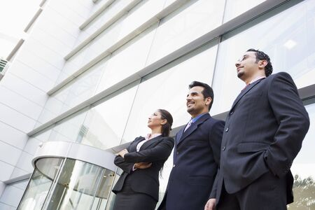 Three businesspeople standing outdoors by building smiling (high key/selective focus) Stock Photo - 3171233