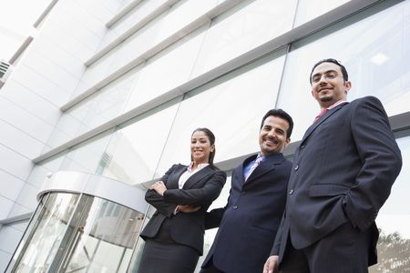 offset view: Three businesspeople standing outdoors by building smiling (high keyselective focus) Stock Photo
