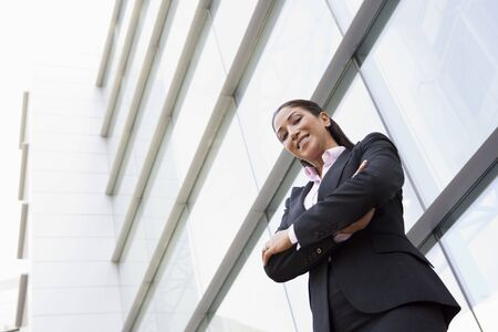 Businesswoman standing outdoors by building smiling (high key/selective focus) Stock Photo - 3171178