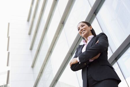 Businesswoman standing outdoors by building smiling (high key/selective focus) Stock Photo - 3171173