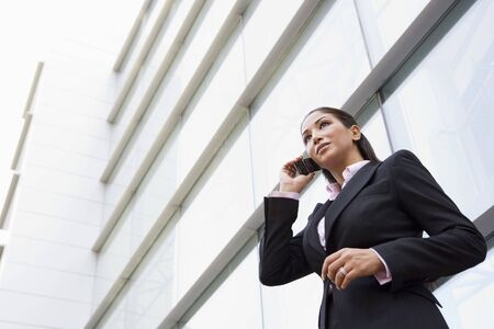 Businesswoman standing outdoors by building on cellular phone (high keyselective focus) photo
