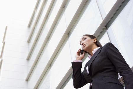 mobilephones: Businesswoman standing outdoors by building on cellular phone (high keyselective focus)