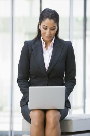 Businesswoman sitting outdoors by building with laptop (high key/selective focus) photo