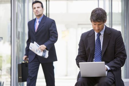 Businessman outdoors in front of building using laptop with businessman in background carrying newspaper (high keyselective focus)
