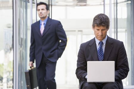 Businessman outdoors in front of building using laptop with businessman in background (high keyselective focus)