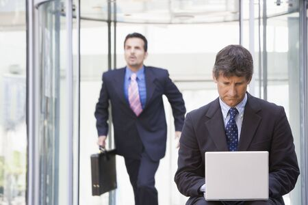 Businessman outdoors in front of building using laptop with businessman running in background (high keyselective focus)