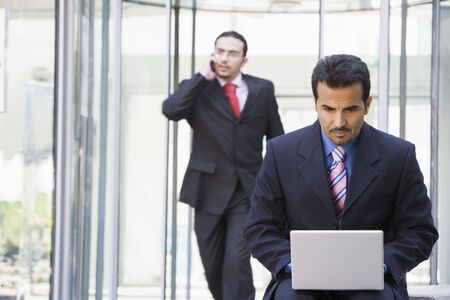 Businessman outdoors in front of building using laptop with businessman in background on cellular phone (high keyselective focus) photo
