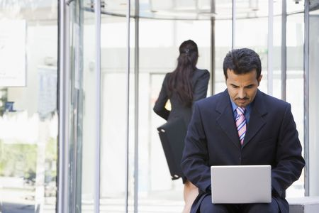 Businessman outdoors in front of building using laptop with businesswoman in background (high keyselective focus) photo