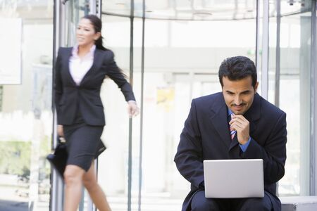 Businessman outdoors in front of building using laptop with businesswoman in background smiling (high key/blur) photo