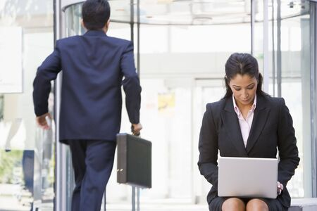 entrance door: Businesswoman outdoors in front of building using laptop with businessman in background (high keyblur) Stock Photo
