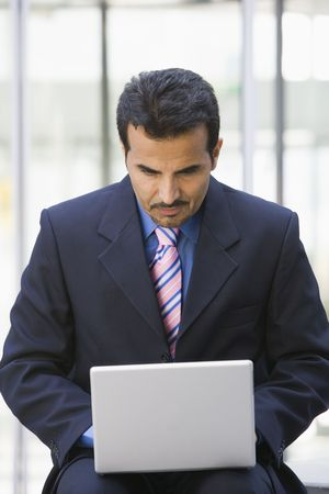 Businessman sitting outdoors by building with a laptop (high key/selective focus) photo