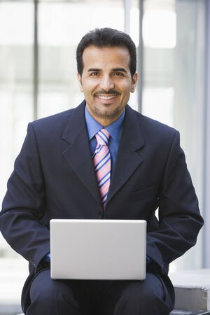 Businessman sitting outdoors by building with a laptop smiling (high key/selective focus) photo