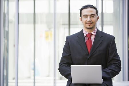 Businessman sitting outdoors by building with a laptop smiling (high keyselective focus) photo