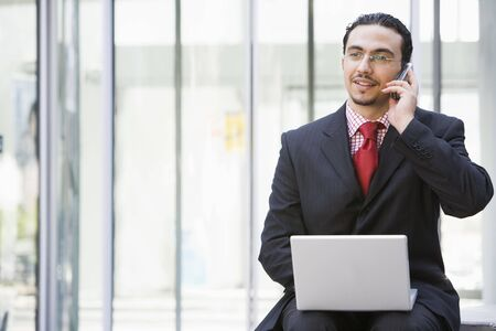 Businessman sitting outdoors by building with a laptop on cellular phone (high keyselective focus) photo