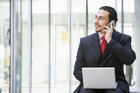 mobilephones: Businessman sitting outdoors by building with a laptop on cellular phone (high keyselective focus)