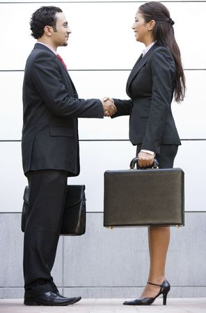 Two businesspeople shaking hands outdoors holding briefcases and smiling photo