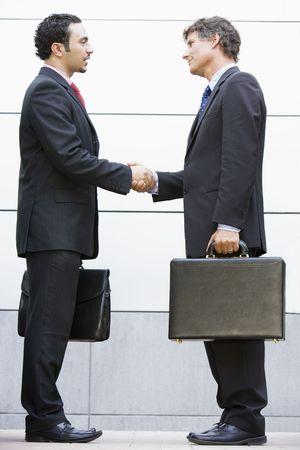 manos estrechadas: Dos hombres de negocios darle la mano al aire libre la celebración de maletines y sonriente  Foto de archivo