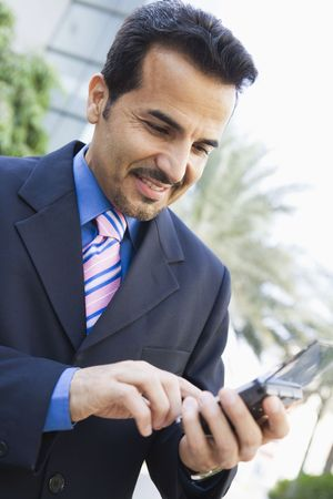 Businessman outdoors using personal digital assistant and smiling (high key/selective focus) photo