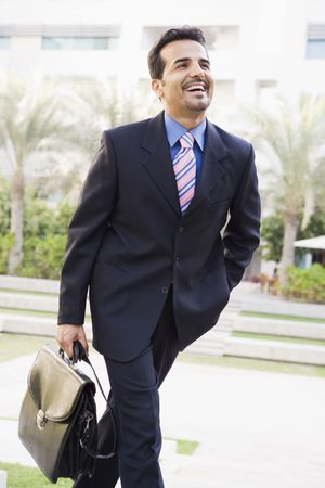 Businessman walking outdoors by building with a briefcase smiling (high key/selective focus) photo