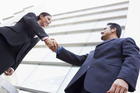 manos estrechadas: Dos hombres de negocios al aire libre mediante la construcción de darle la mano y sonriendo (clave de alta  selectiva enfoque)  Foto de archivo