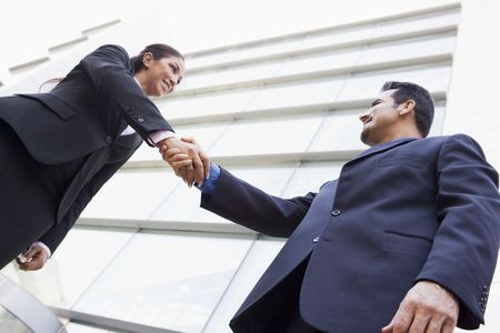 handshakes: Two businesspeople outdoors by building shaking hands and smiling (high keyselective focus)