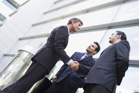 Three businessmen outdoors by building shaking hands and smiling (high keyselective focus)