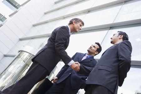 manos estrechadas: Tres hombres de negocios al aire libre mediante la construcci�n de darle la mano y sonriendo (clave de alta  selectiva enfoque)  Foto de archivo